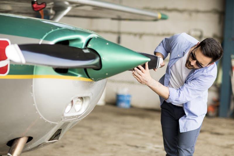 Молодой пилотный проверяя самолет в ангаре стоковая фотография rf