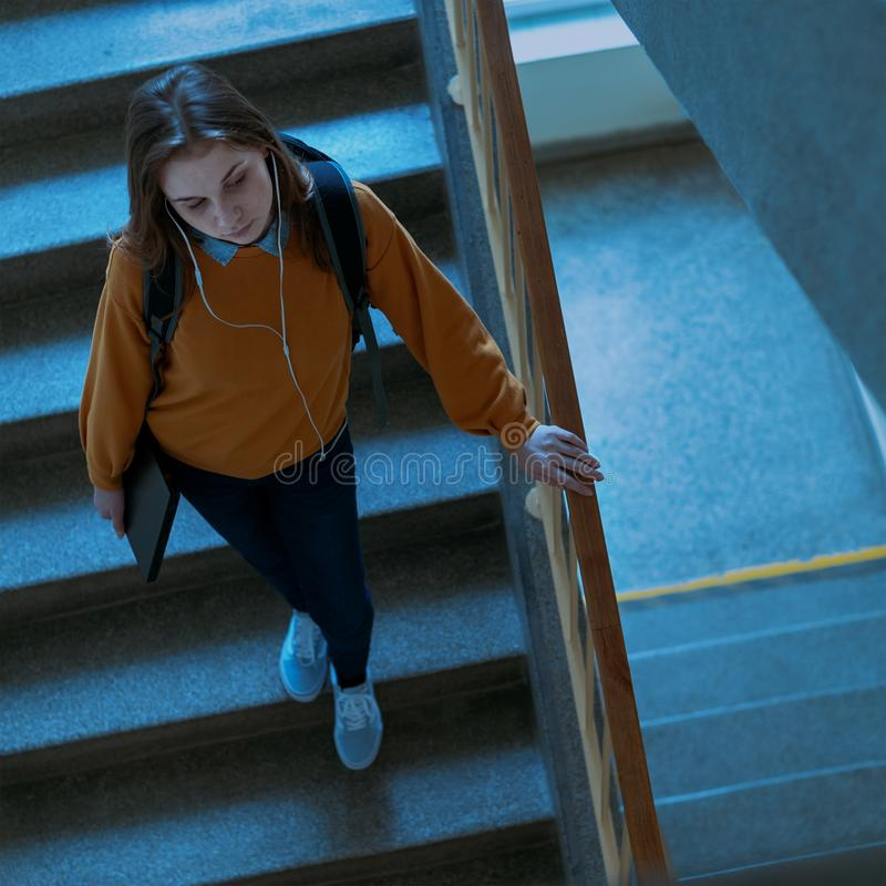 Молодой подавленный сиротливый женский студент колледжа идя вниз с лестниц на ее школе, смотря вниз Задирающ, концепция депрессии стоковая фотография
