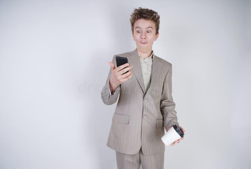 Молодой подросток с удивленными эмоциями в серых одеждах дела стоя с мобильным телефоном и бумажным стаканчиком кофе на белой сту стоковое фото
