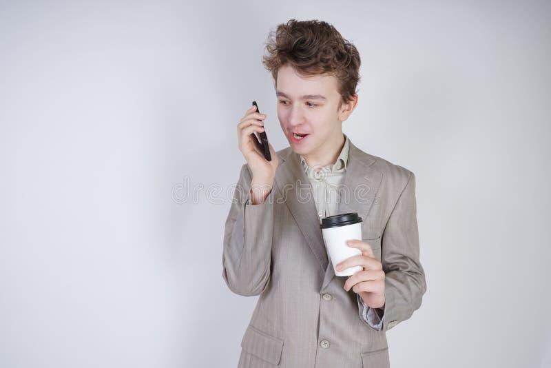Молодой подросток с удивленными эмоциями в серых одеждах дела стоя с мобильным телефоном и бумажным стаканчиком кофе на белой сту стоковые изображения