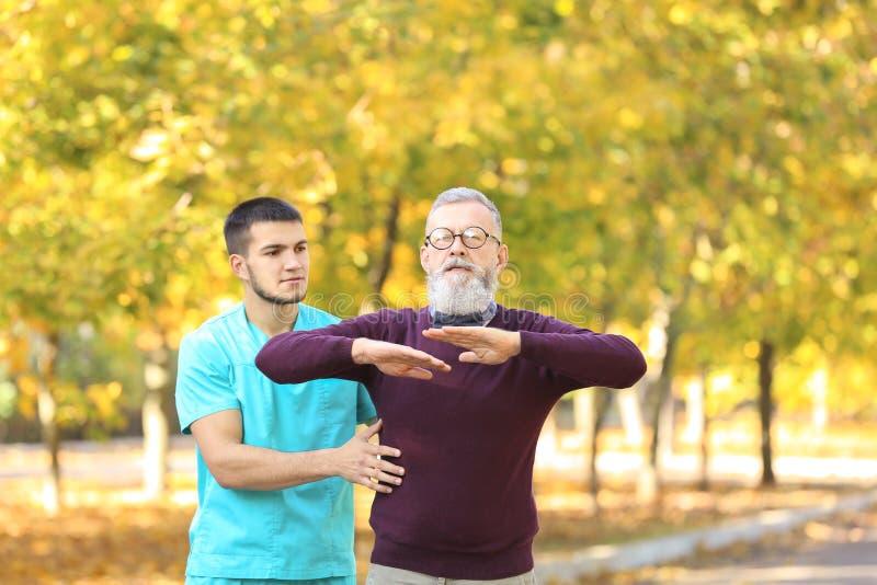 Молодой попечитель идя с старшим человеком стоковая фотография rf