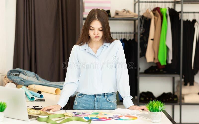 Молодой портной выбирая цвет для новой рубашки и имея сомнения в atelier стоковые изображения rf
