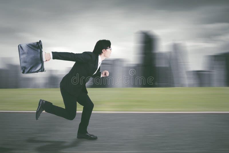 Молодой предприниматель бежать на дороге стоковое изображение