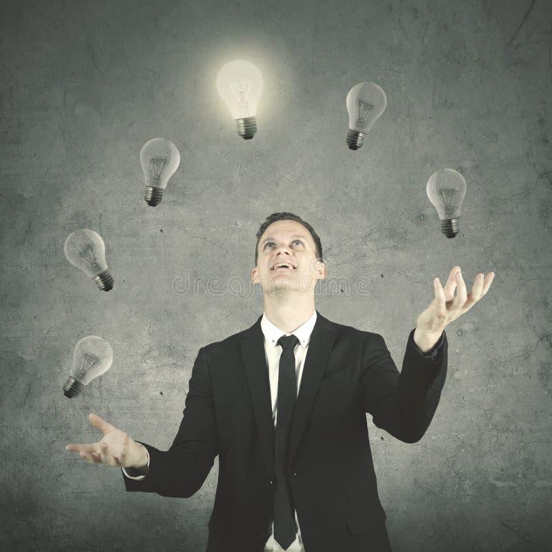 Молодой предприниматель жонглируя много электрических лампочек стоковые изображения