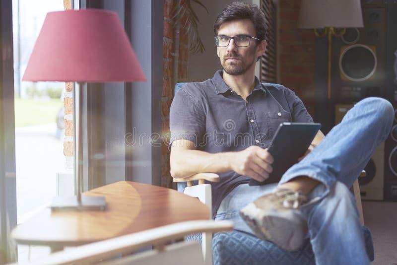 Молодой предприниматель работая на запуске в современном офисе используя цифровую таблетку Укомплектуйте личным составом нося сте стоковые фото