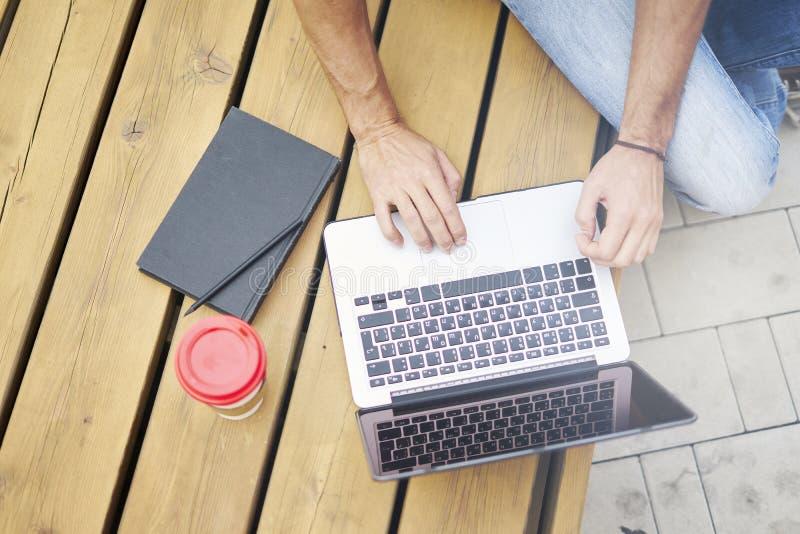 Молодой предприниматель работая на парке снаружи на деревянной скамье Взгляд крупного плана выше рук человека на клавиатуре компь стоковые изображения rf
