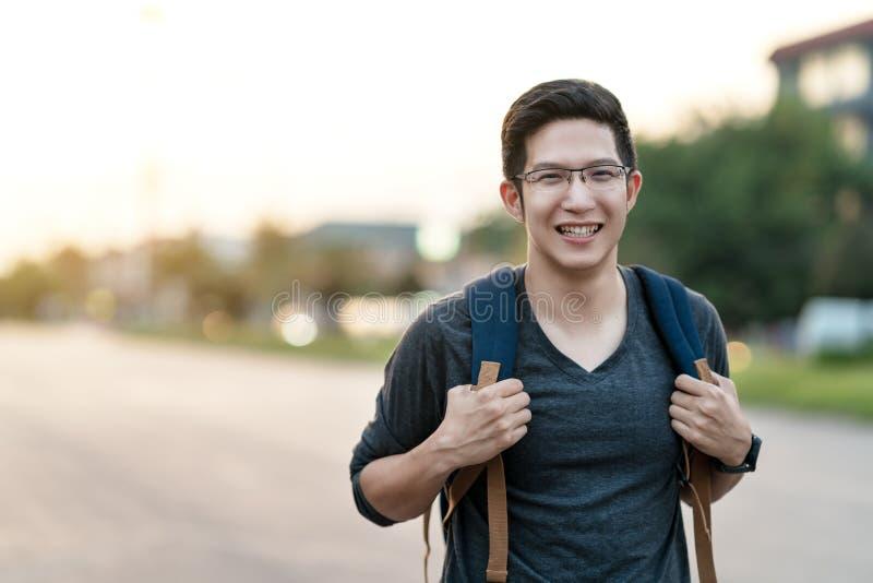 Молодой привлекательный азиатский рюкзак удерживания человека или парня коллежа усмехаясь на каникулах чувства камеры возбужденны стоковое фото rf