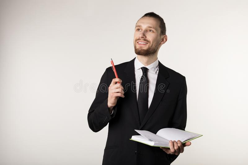 Молодой привлекательный бородатый учитель в черной тетради удерживания костюма и связи и ручка в руках стоковое фото rf