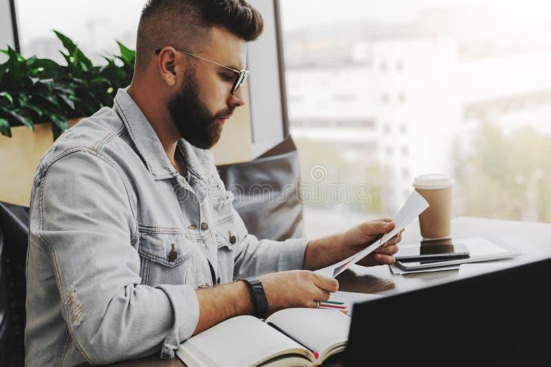 Молодой привлекательный бородатый человек хипстера сидит в кафе перед aptop, читая печатные документы Фрилансер работает удаленно стоковые фотографии rf