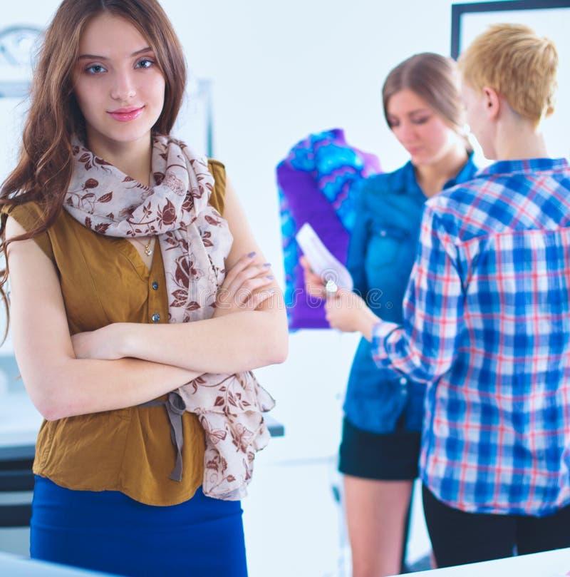 Молодой привлекательный женский модельер работая на столе офиса, рисуя пока говорящ на черни стоковое изображение