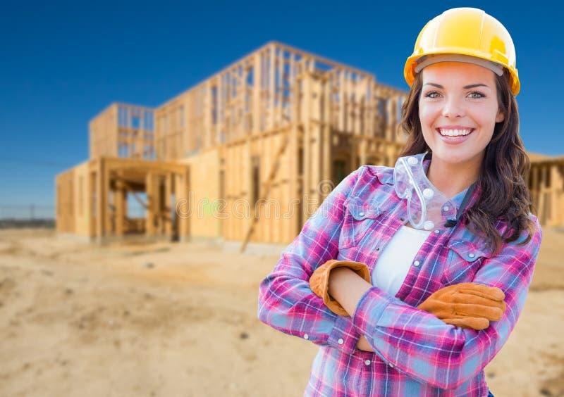 Молодой привлекательный женский рабочий-строитель носит перчатки и защитный шлем стоковая фотография