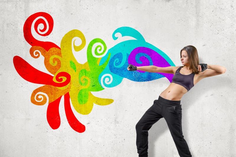 Молодой привлекательный женский танцор в черных безрукавных верхней части урожая и танцах sweatpants около белой стены с красочны стоковые фотографии rf