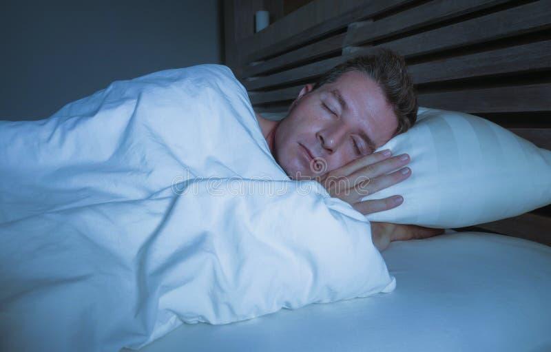 Молодой привлекательный и красивый утомленный человек на его 30s или 40s в спать кровати покрытый с одеялом мирно и ослабленный н стоковые изображения rf