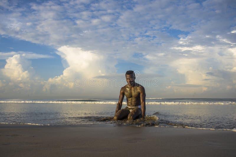 Молодой привлекательный и сексуальный черный афро американский человек с сексуальным мышечным телом вставая на колени на красивый стоковое фото