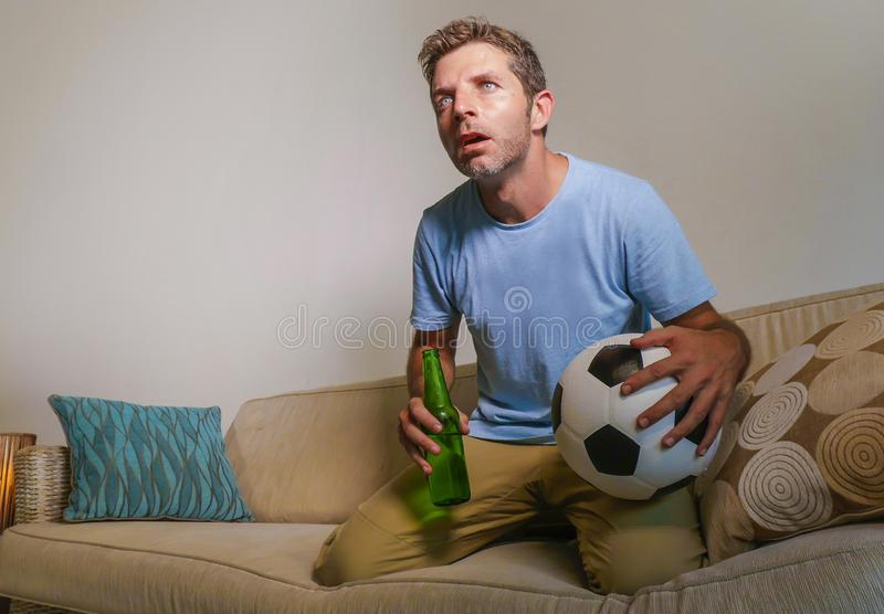 Молодой привлекательный и слабонервный человек сконцентрировал смотреть футбольную игру на телевидении держа пивную бутылку и фут стоковые изображения rf