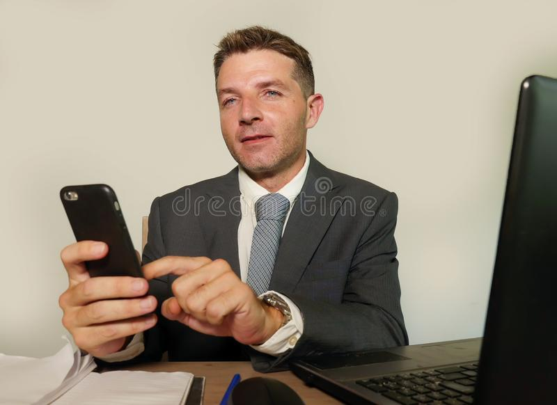 Молодой привлекательный и счастливый бизнесмен в деятельности костюма и галстука на столе ноутбука офиса используя мобильный теле стоковое фото