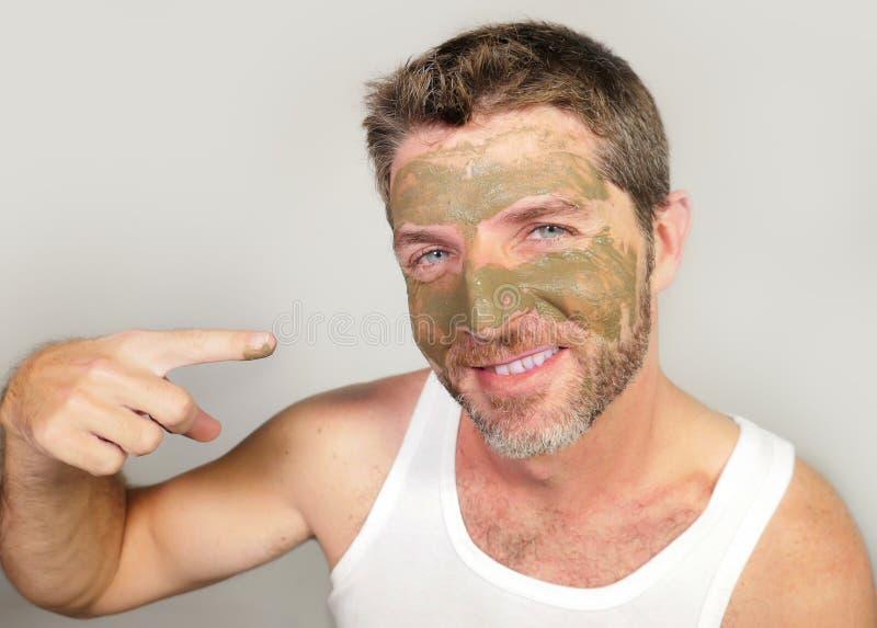Молодой привлекательный и счастливый человек смеясь над смотрящ себя в зеркале смешном с зеленой сливк на его стороне прикладывая стоковые фотографии rf