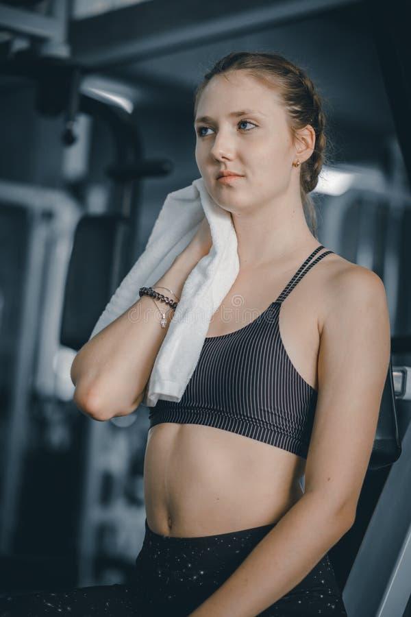 Молодой привлекательный кавказец женщины сидя и используя полотенце для того чтобы обтереть пот стоковое изображение rf