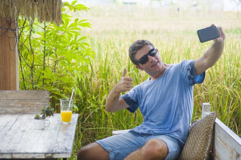 Молодой привлекательный кавказский человек 30s усмехаясь счастливое и расслабленное усаживание на кофейне поля риса в отключении  стоковое фото rf