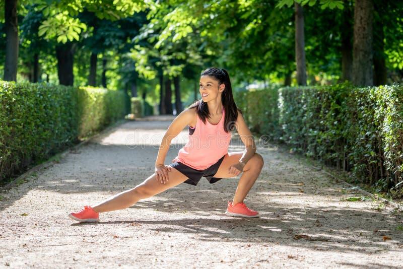 Молодой привлекательный латинский женский протягивать перед ей разрабатывает бег в современном парке стоковые фото