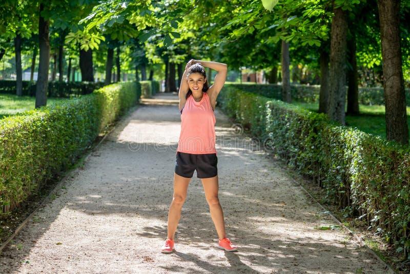 Молодой привлекательный латинский женский протягивать перед ей разрабатывает бег в современном парке стоковые изображения rf