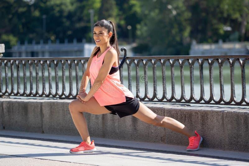 Молодой привлекательный латинский женский протягивать перед ей разрабатывает бег в современном парке стоковое изображение