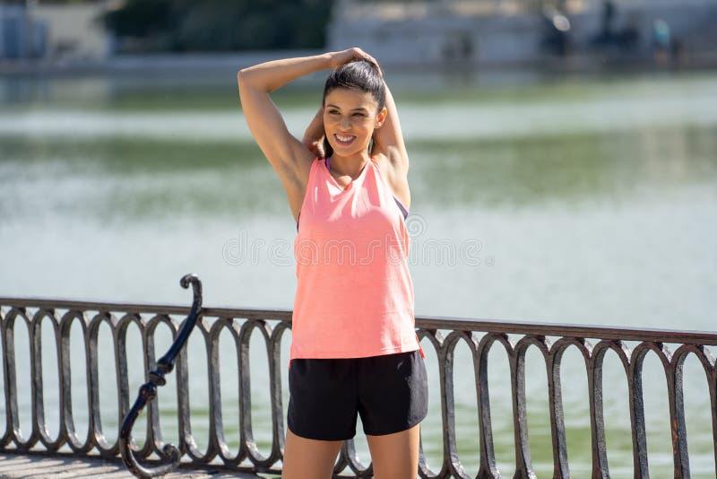 Молодой привлекательный латинский женский протягивать перед ей разрабатывает бег в современном парке стоковая фотография rf