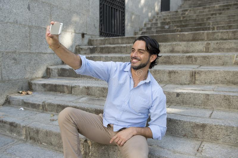 Молодой привлекательный латинский человек на лестнице города фотографируя selfie имея потеху на мобильном телефоне стоковая фотография rf