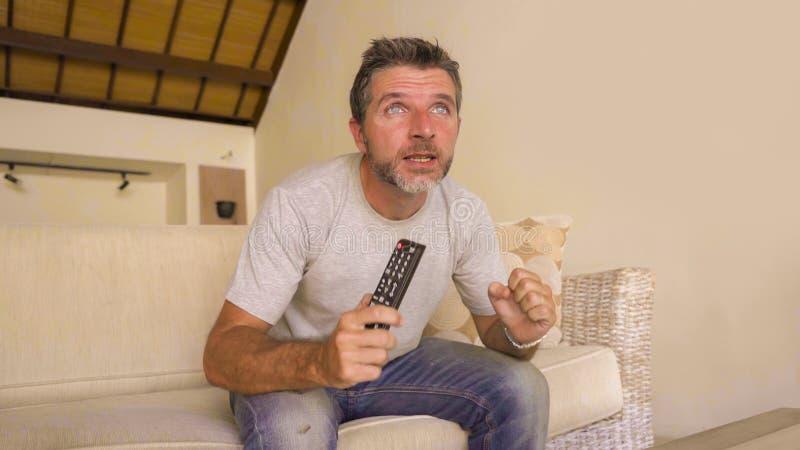 Молодой привлекательный нервный и возбужденный человек сидя дома кресло живущей комнаты держа футбольный матч или приостановку ТВ стоковые изображения