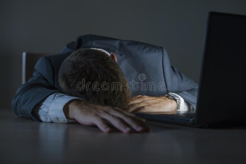 Молодой привлекательный расточительствованный и уставший человек предпринимателя спать принимающ ворсину ночную на столе ноутбука стоковые изображения rf