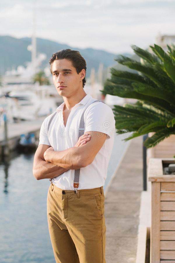 Молодой привлекательный стильный человек идет вдоль пристани с яхтами и гостиницами Портрет мыжской модели стоковые изображения