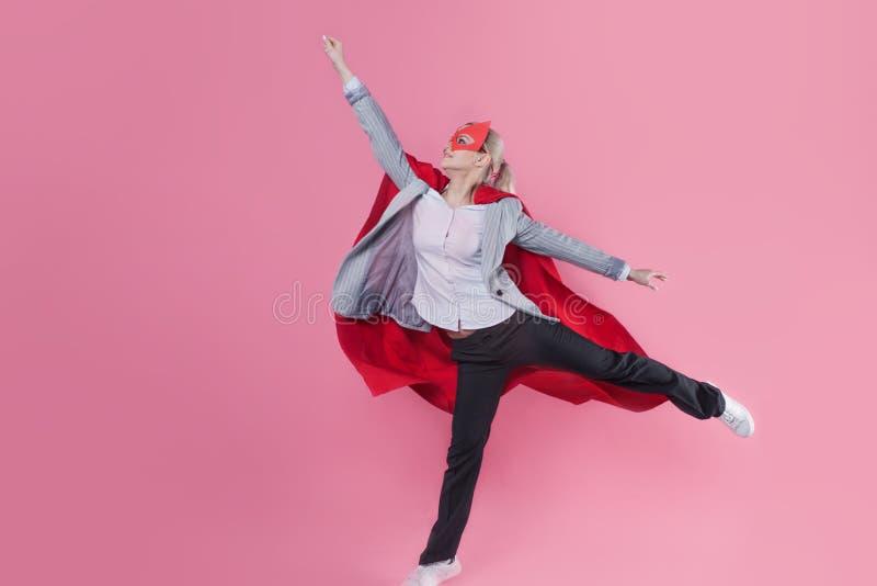 Молодой привлекательный супергерой женщины Девушка в деловом костюме и маска с красным плащем героя стоковое фото