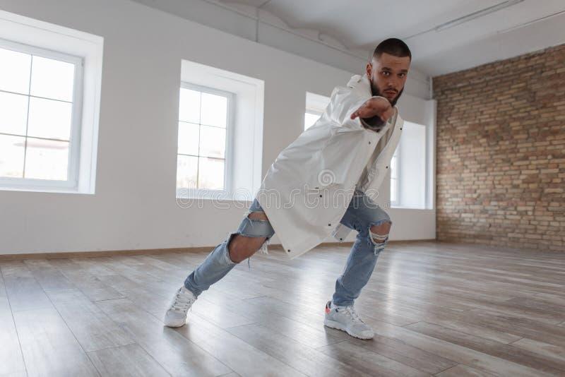 Молодой привлекательный танцор в ультрамодной куртке и сорванных джинсах стоковое фото rf