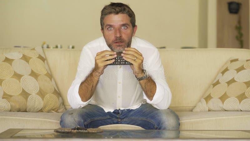 Молодой привлекательный удивленный и сотрясенный человек смотря телевизионные сообщения или изумляя фильм на кресле софы живя ком стоковые фотографии rf