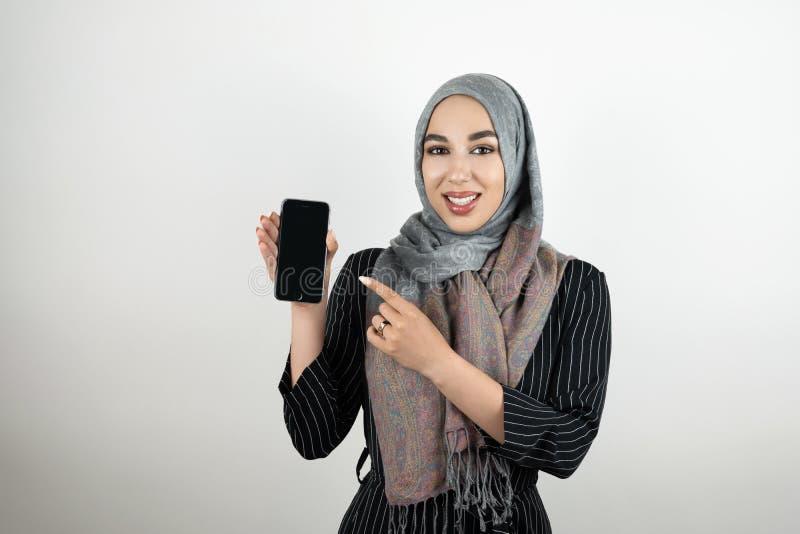 Молодой привлекательный усмехаясь показ головного платка hijab тюрбана мусульманского студента нося и указывать на смартфон с ей стоковые изображения rf