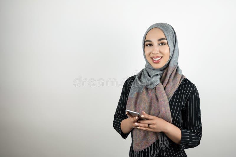 Молодой привлекательный усмехаясь смартфон удерживания головного платка hijab тюрбана мусульманской женщины нося в ее руках изоли стоковые изображения rf
