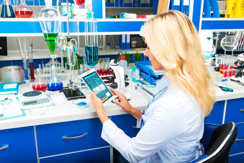 Молодой привлекательный ученый женщины используя планшет в Ла стоковые фото
