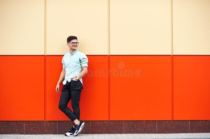 Молодой привлекательный человек в голубой рубашке, солнечных очках, стоя рядом с оранжевой предпосылкой стены стоковая фотография rf