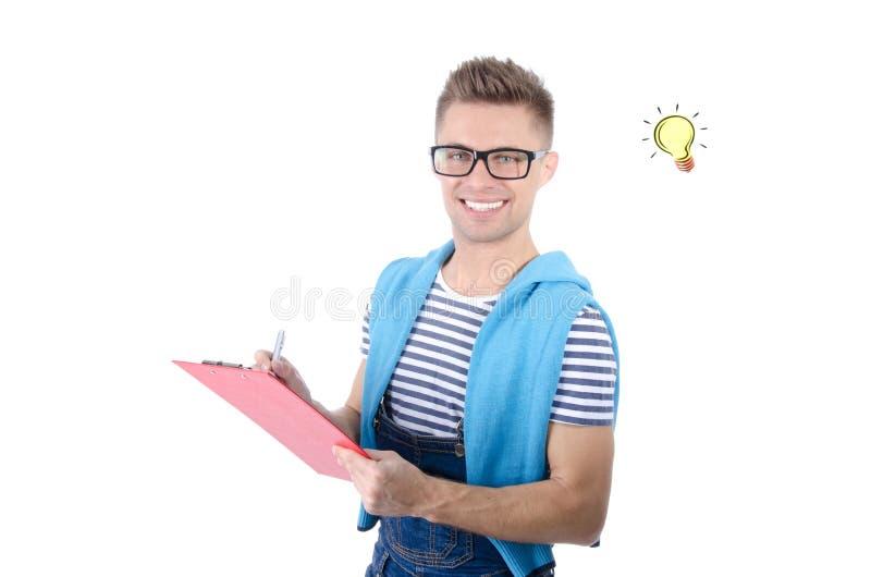 Молодой привлекательный человек держа доску сзажимом для бумаги Улыбка и утеха стоковые изображения rf