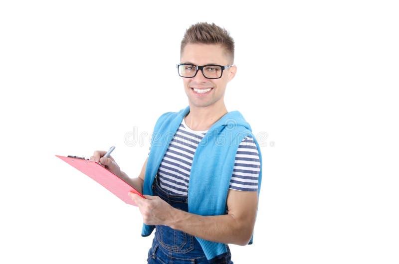 Молодой привлекательный человек держа доску сзажимом для бумаги Улыбка и утеха стоковое фото