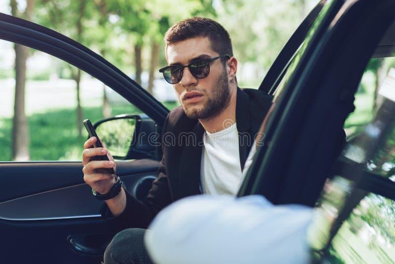 Молодой привлекательный человек используя мобильный телефон в его автомобиле стоковое фото rf