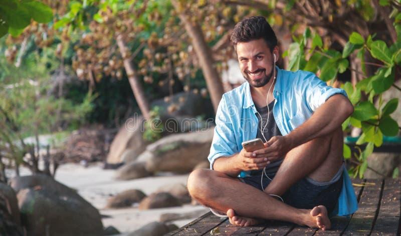 Молодой привлекательный человек латиноамериканца парня смешанной гонки с бородой слушая музыку на наушниках, outdoors стоковая фотография rf