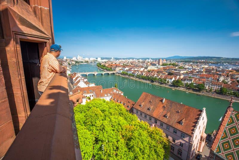 Молодой привлекательный человек наслаждаясь взглядом к старому центру города Базеля от собора Мунстер, Швейцарии, Европы стоковая фотография rf