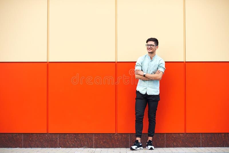 Молодой привлекательный человек нося голубую рубашку и eyeglasses, стоя с п стоковая фотография