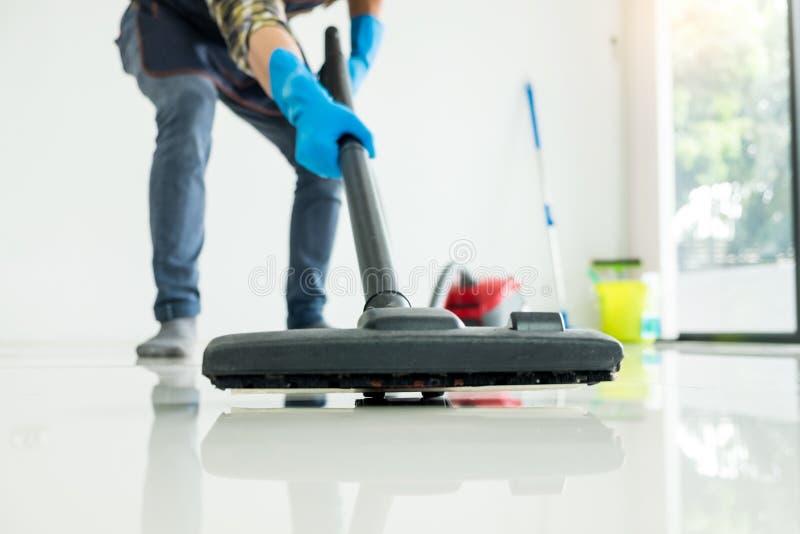 Молодой привлекательный человек очищает оборудование вакуума коммерчески очищая на поле дома помогая жене стоковое изображение rf