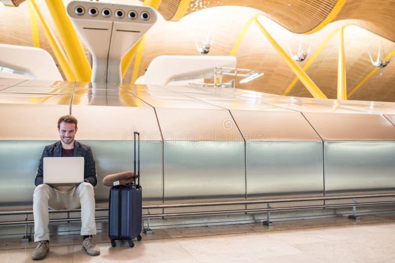 Молодой привлекательный человек сидя на авиапорте работая с lapto стоковые изображения