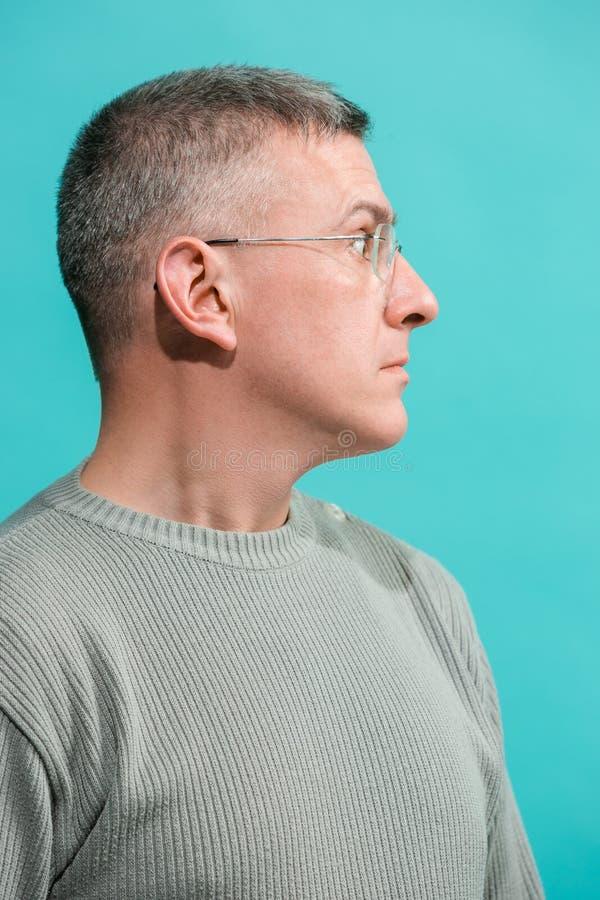 Молодой привлекательный человек смотря удивленный изолированный на сини стоковое фото rf