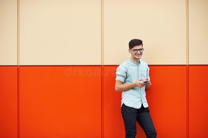 Молодой привлекательный человек smilling и используя мобильный телефон в улице стоковое изображение rf
