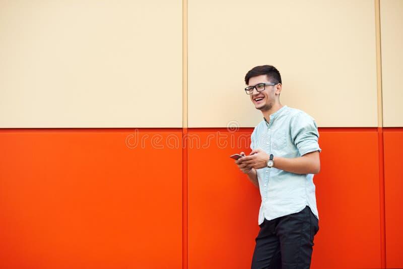 Молодой привлекательный человек smilling и используя мобильный телефон в  стоковое изображение