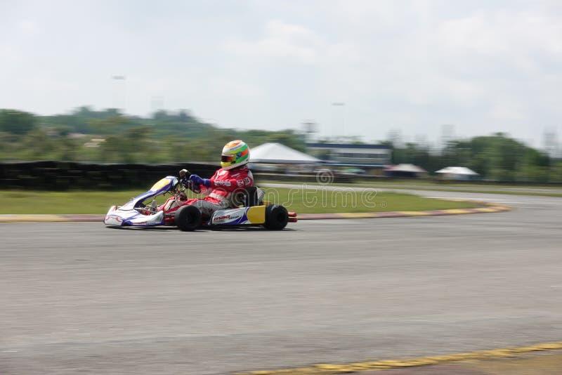 Молодой профессиональный гонщик с состязаться с его идет-kart в конкуренцию стоковые фотографии rf